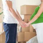 Cute pregnant wife holding hands of  her husband standing front of boxes during moving in new home